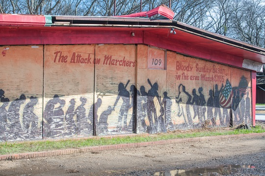"""mural in Selma, Alabama: silhouette figures, flag, text """"The Attack on Marchers - 109 - Bloody Sunday Began in this area March 7, 1965."""""""
