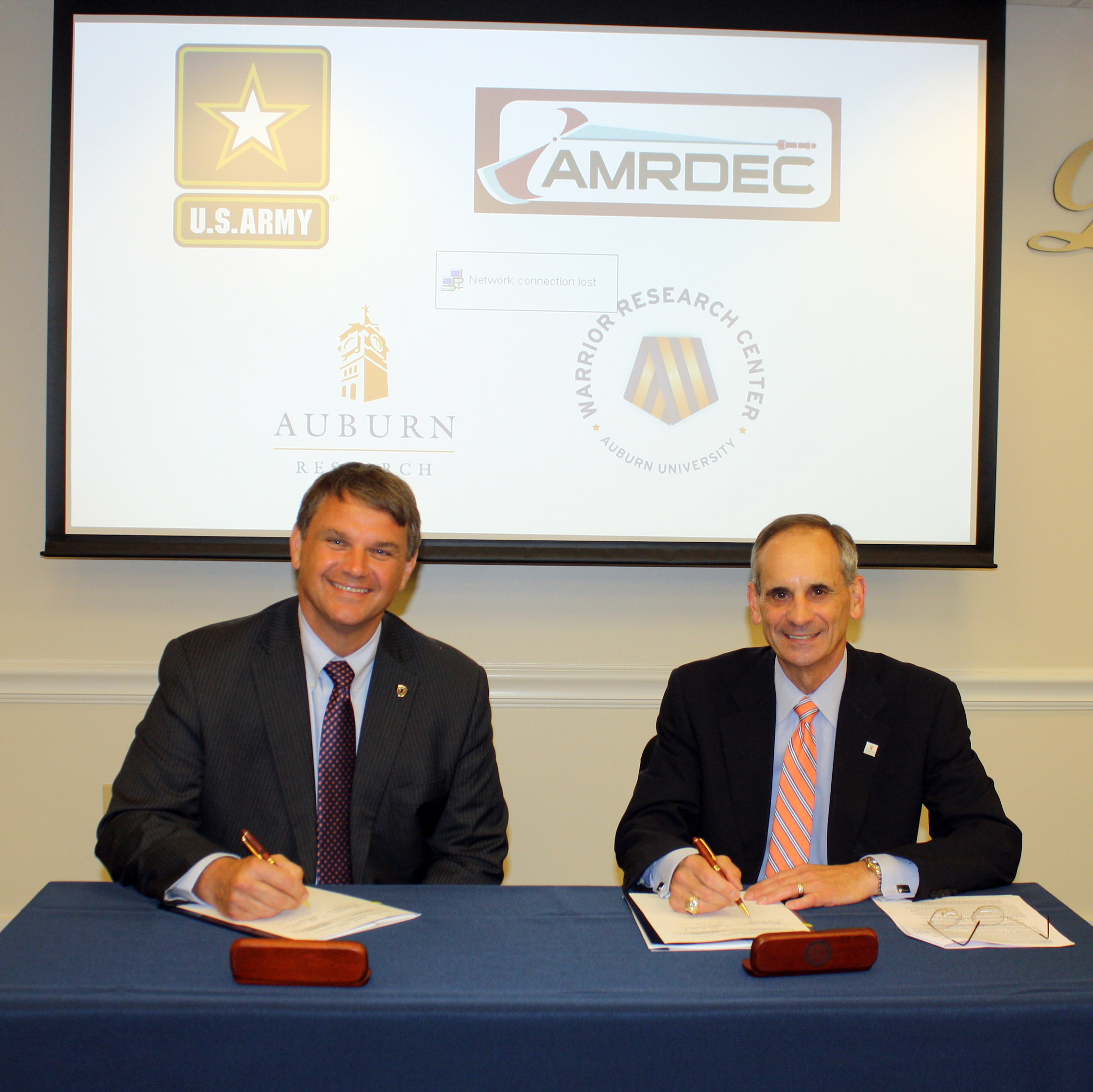Jeff Langhout, left, acting technical director of the U.S. Army's Aviation and Missile Research, Development and Engineering Center, signs a cooperative research and development agreement with John Mason, Auburn's vice president for research and economic development.