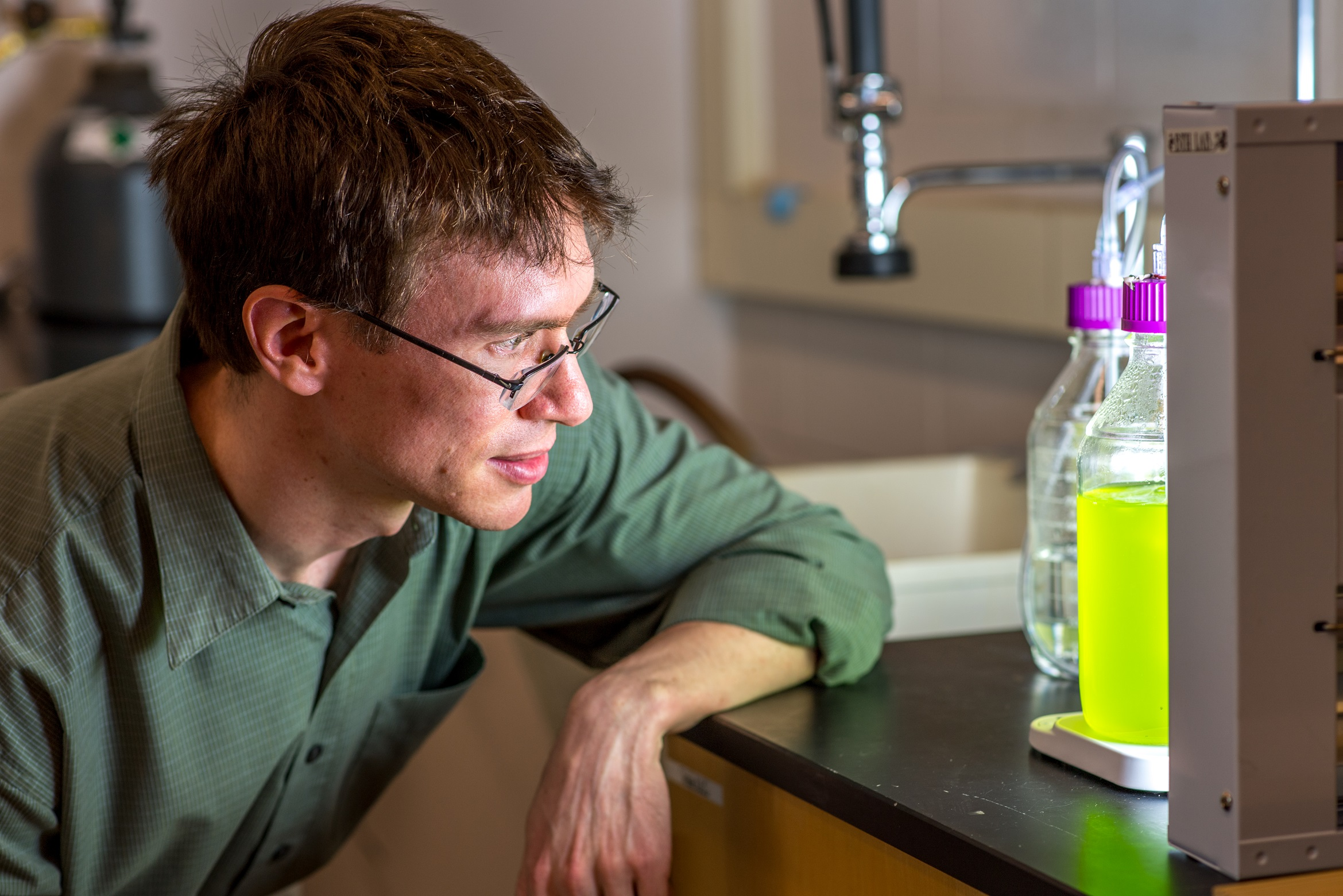 Brendan Higgins examines Chlorella algae in his lab.